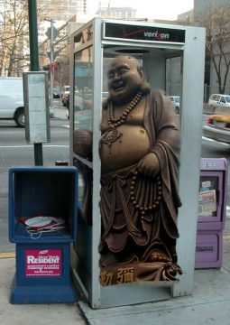 Bronze Buddha statue with big belly stuck in street-corner phone booth