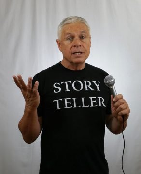 Ned Buratovich wearing Story Teller T-shirt and holding a microphone, expounding on something or other.