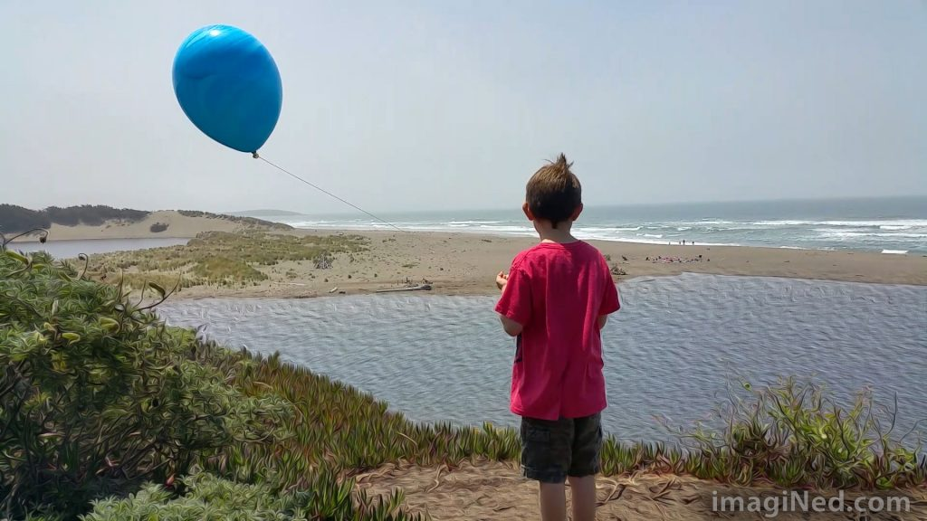 A young boy in shorts and a red T-shirt on a bluff, overlooking the ocean, staring out to sea, while his windblown blue balloon flies off to the side.