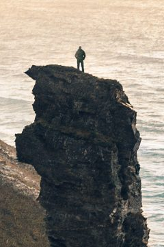 Telephoto shot of a man standing atop a tall, rocky spire, overlooking the ocean