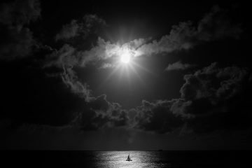 Dramatic grayscale photo of full moon shining through dark clouds illuminating the sea below.