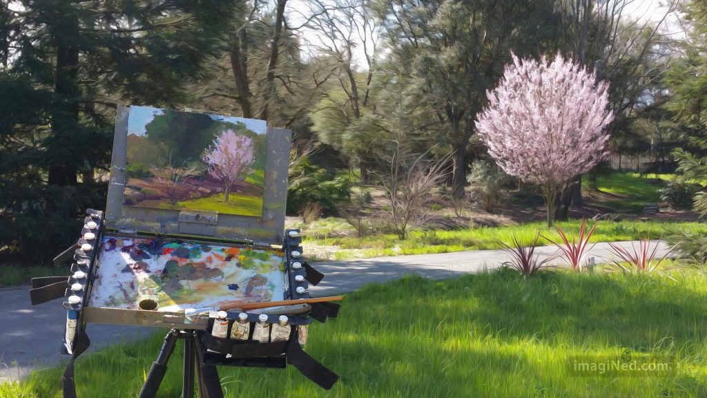 A flowering plum tree bursts into a riot of pink blossoms in the background. In the foreground, an artist's easel with the partly painted scene upon it captures the artist's impression.