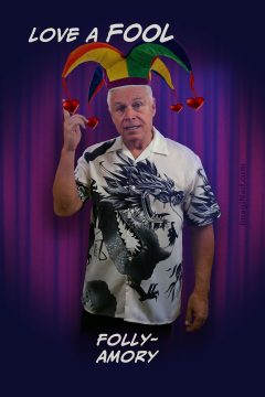 Ned wearing Oriental dragon print shirt and a jester's or fool's cap with four multi-colored peaks from which small red hearts dangle on red ribbons, standing in front of nightclub stage curtain pointing up, as if to make a point. The associated text is positioned above and below his image.