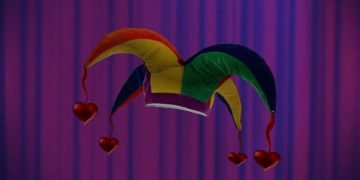 Jesters cap with hearts in front of stage curtain.
