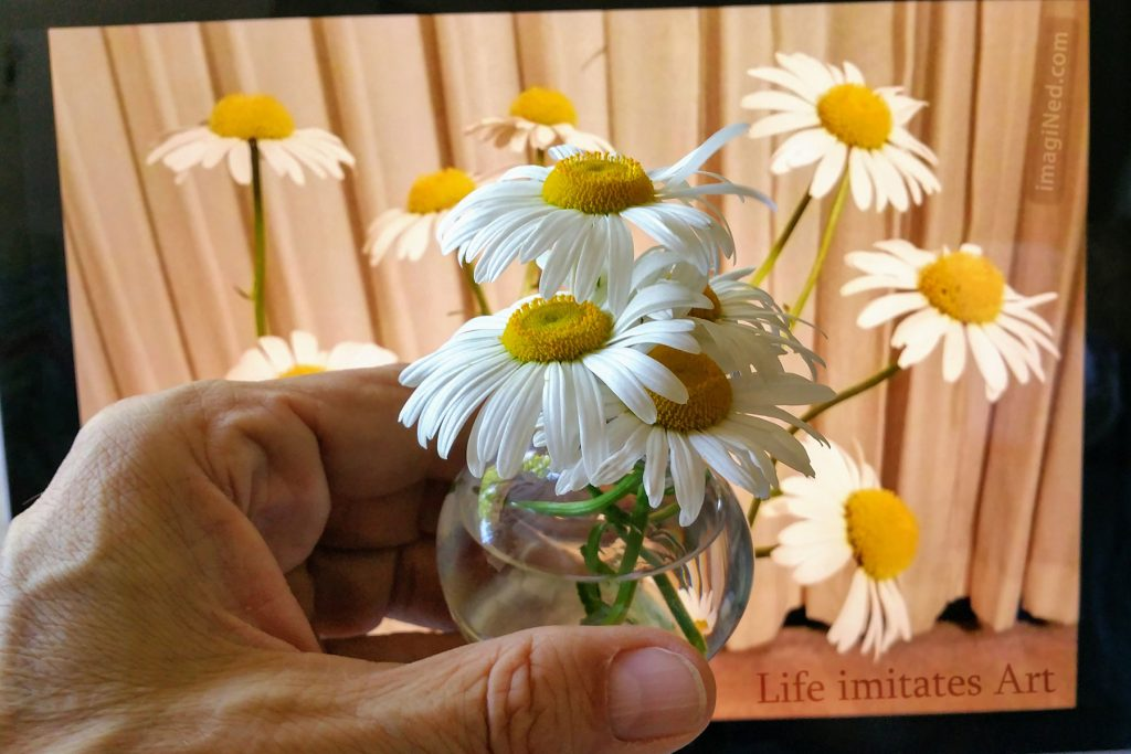A man's hand holds a small, globular, glass vase with four or five short-stemmed daisies in it in front of a laptop screen filled with a photo of a larger bouquet of daisies in front of a beige curtain.