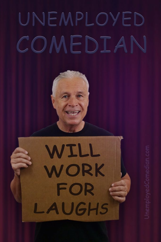 """Ned Buratovich on the stage holding a cardboard sign saying, """"WILL WORK FOR LAUGHS"""" underneath the lettering saying """"UNEMPLOYED COMEDIAN"""""""