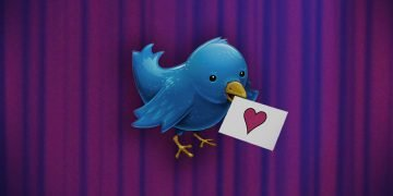 Against a stage curtain background, a blue Twitter Bird hold a love note (with a red heart) in his beak