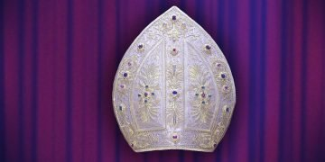 Pope's mitre hat against a stage curtain background