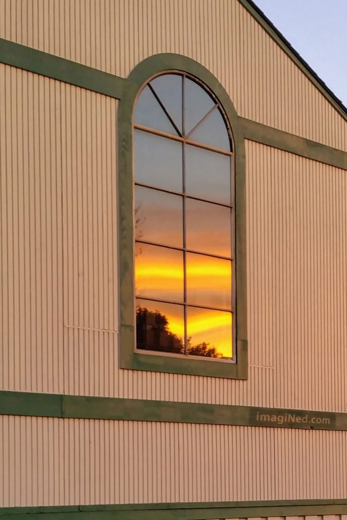 Bright yellow streaks glow through dusky orange cloud cover as seen reflected in a large arched window.