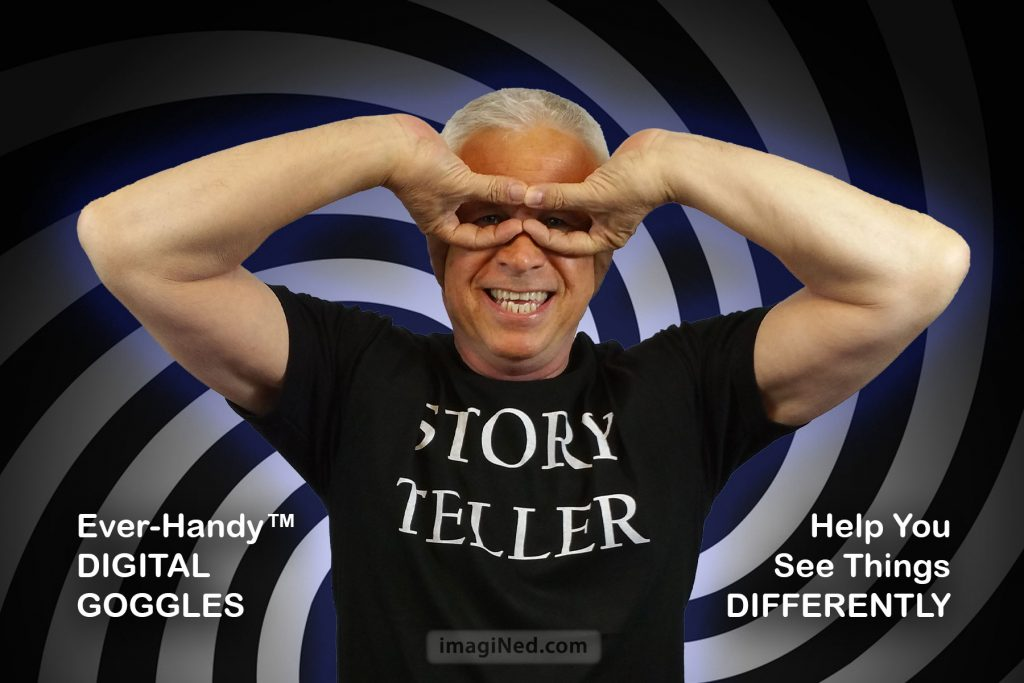 Ned Buratovich wearing STORY TELLER T-shirt, making goggles with thumb and forefinger of each hand, elbows up, palms against his temples.