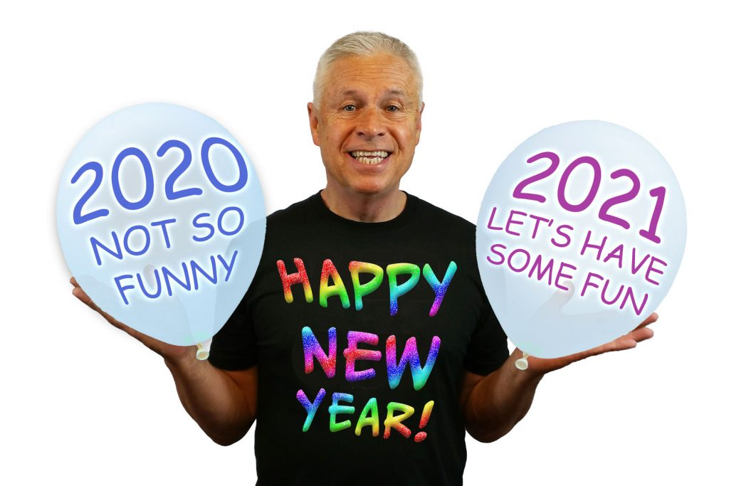Ned Buratovich, wearing a T-shirt with rainbow-colored lettering saying, HAPPY NEW YEAR, and holding a big balloon in each hand. One balloon says, 2020 NOT SO FUNNY. The other says, 2021 LET'S HAVE SOME FUN.