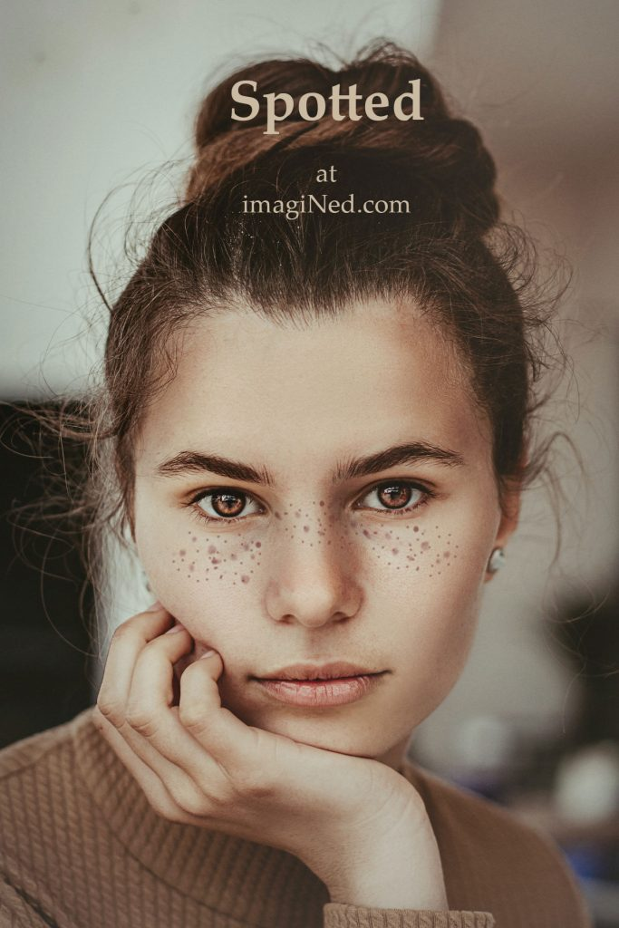 Close-up portrait photo of pretty, young brown-eyed woman with interesting freckle pattern beneath her eyes.