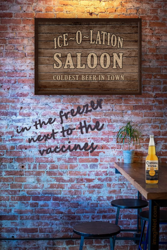 """A wooden sign saying, """"ISO-O-LATION SALOON - COLDEST BEER IN TOWN"""" hangs on a brick wall, upon which is spray painted, """"in the freezer, next to the vaccines."""""""