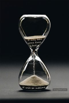 Close up of grains of sand flowing through an hourglass.