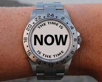 "Closeup of Rolex watch on person's wrist. Watch face has the word, ""NOW"" in bold letters."