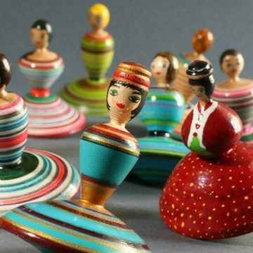 A half-dozen toy tops painted like women with flared skirts sit on a table top.